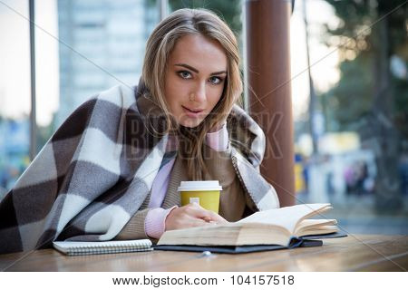 Portrait of a happy girl sitting with book in cafe and looking at camera
