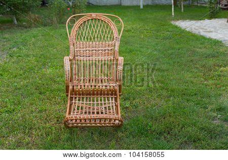 Empty wicker rocking-chair in the garden