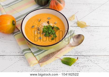 Pumpkin soup on white wooden background