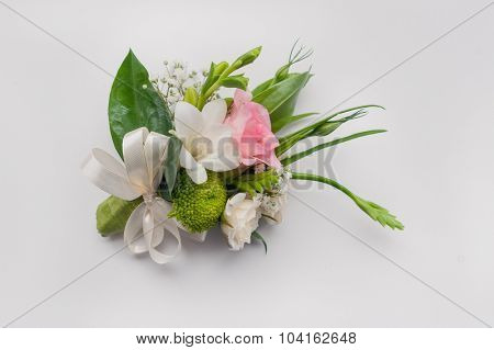 boutonniere with pink rose and white freesia for groom