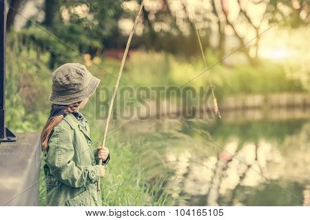 little fisher girl with rod near a river