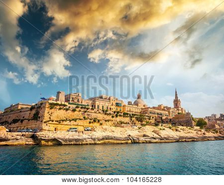 view on Valletta with its architecture from the sea at sunset