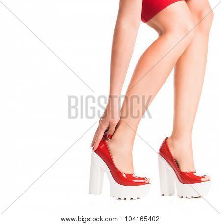girl touching legs in shoes with hand