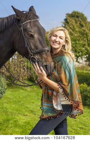 Beautiful happy woman wearing poncho, smiling and leading her horse in sunshine