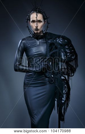 Beautiful Woman In Black Gothic Dress. The Face Wearing A Mask.