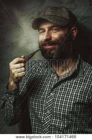 Portrait Of Young Stylish Man With A Beard With A Pipe