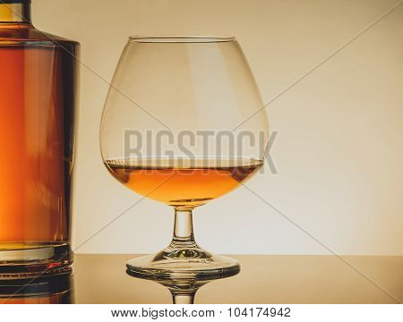 Snifter Of Brandy In Elegant Typical Cognac Glass Near Bottle On Table, Warm Style