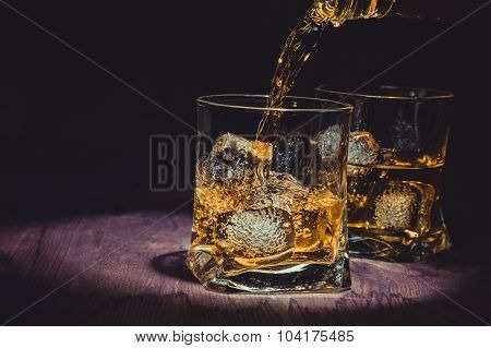 Barman Pouring Whiskey In Two Glasses On Wood Table, Warm Atmosphere, Old Style, Time Of Relax With