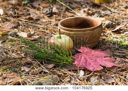 A Wooden Plate With Heather, Apple And Red Leaves