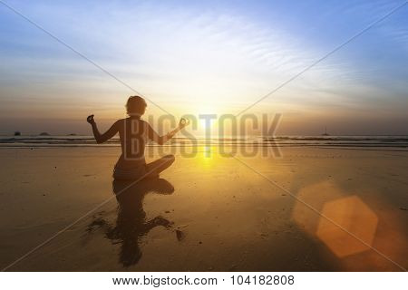 Beautiful girl sitting on beach during sunset and meditating in yoga pose.