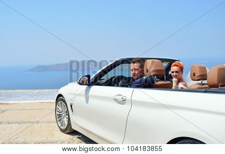 Beautiful young couple bride and groom posing in white cabriolet