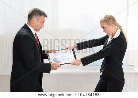 Businesspeople Pulling Clipboard With Graph Paper
