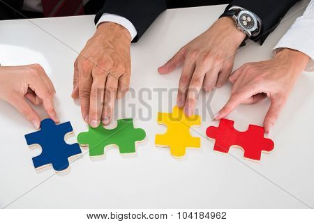 People Assembling Puzzle Pieces