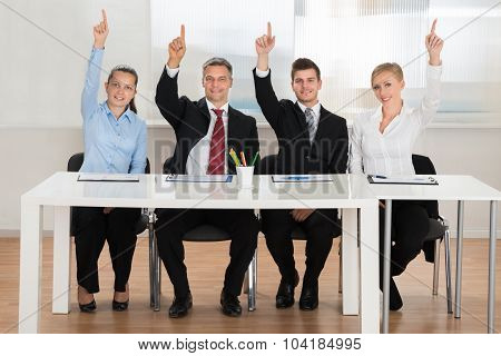 Businesspeople Raising Hands In Conference