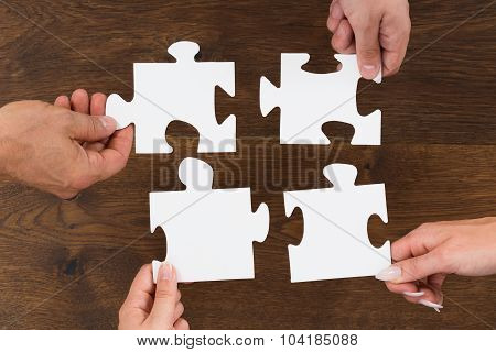 Human Hands Connecting Puzzle Piece