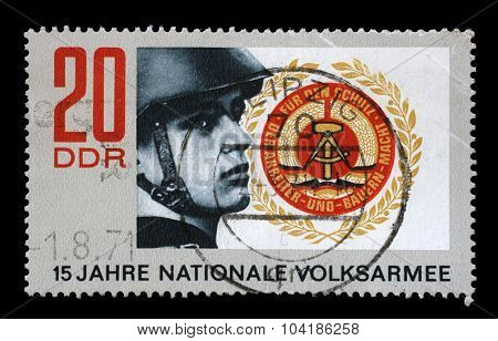 GDR-CIRCA 1971: A stamp printed in GDR from the 15 years National Peoples Army issue shows soldier and coat of arms of GDR, circa 1971.