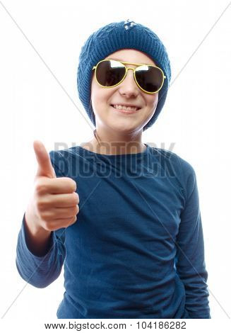 Girl wearing a knitted hat and sunglasses showing thumbs up