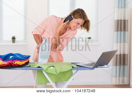 Woman With Electric Iron And Laptop Talking On Mobile Phone