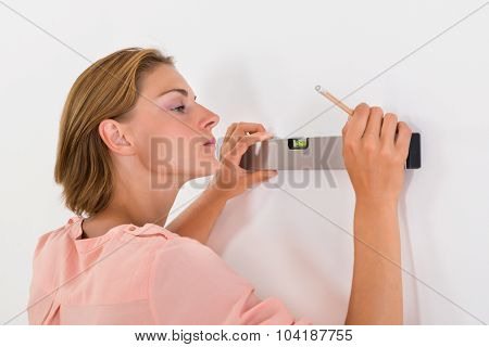 Woman Taking Measurements Of The Wall