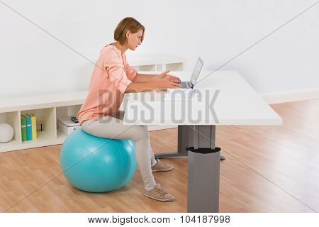 Woman Sitting On Fitness Ball Using Laptop