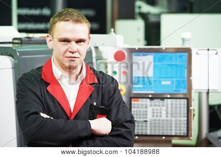 Portrait of mechanical technician service engineer worker at cnc metal machining milling center in tool workshop