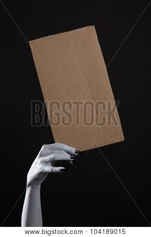 Spooky ghost hand with black nails holding blank cardboard, Halloween theme