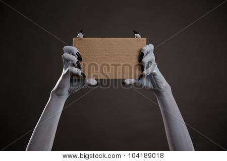 Creepy white hands with black nails holding blank cardboard, Halloween theme