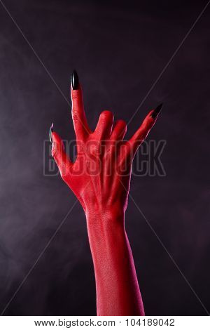 Scary devilish hand showing heavy metal gesture, studio shot on smoky background