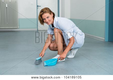 Female Janitor With Brush And Dustpan