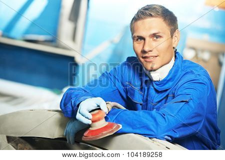 Portrait of auto mechanic worker sanding polishing grinding machine at automobile repair and renew service station