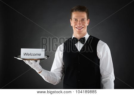 Waiter Holding Plate With Welcome Text On Card