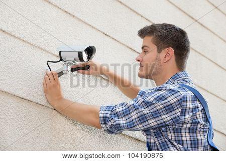 Technician Fixing Cctv Camera On Wall