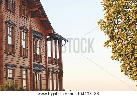 Facade of the building with a log house