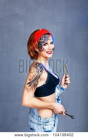 Girl With Face Art Mechanic Holding Spanner And Smiling.