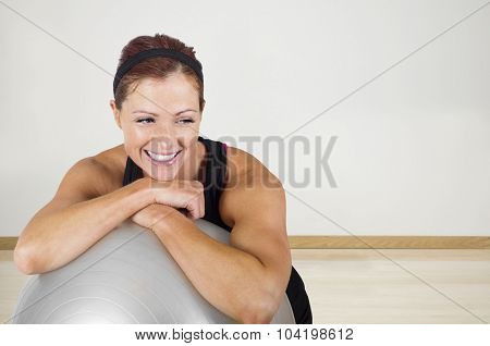 Happy healthy fitness woman resting on a exercise ball. Candid portrait of a smiling woman resting after exercising at an indoor gym