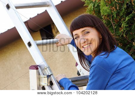 Smiling Woman Climbing On Aluminum Ladder In Garden