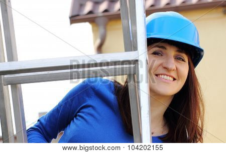 Smiling Woman In Blue Helmet On Aluminum Ladder