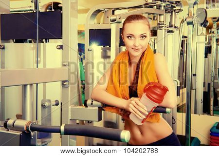 Close-up portrait of a beautiful smiling young woman at the gym. Active lifestyle, bodycare.