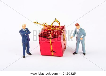 Figurines Of Two Businessmans With Christmas Gift