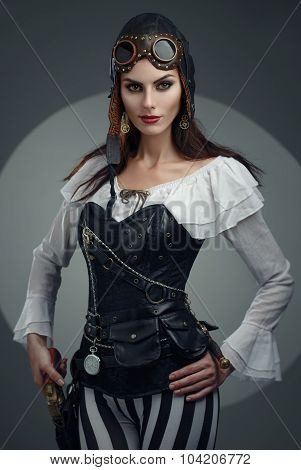 Steampunk. Beautiful Girl Wearing A Helmet, Leather Corset, With A Gun And A Clock On A Chain