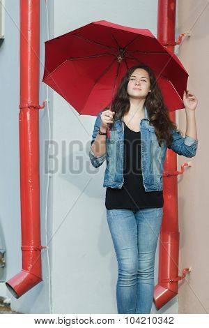 City Portrait Of Pedestrian Girl Holding Plain Red Umbrella And Standing Between Two Red Downpipes