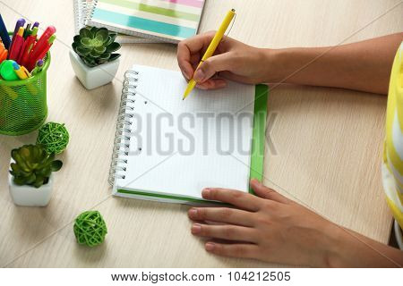 Woman write on notebook on workplace close up