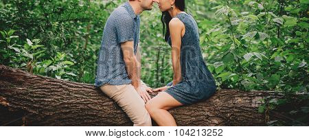 Young Couple In Love Sitting On Tree
