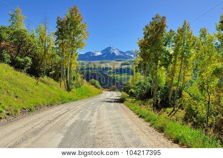 Road Through The Mountains With Colorful Yellow, Green And Red Aspen During Foliage Season