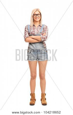 Full length portrait of a hipster girl with large black glasses and a short overalls isolated on white background