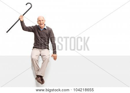 Excited senior gentleman sitting on a blank white signboard and waving his cane isolated on white background