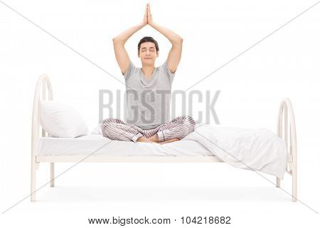 Young man in pajamas meditating seated on a bed with his eyes closed isolated on white background