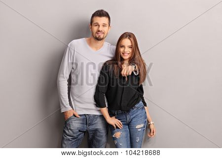 Young man hugging his girlfriend and looking at the camera against a gray wall