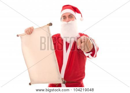 Santa Claus Reading In A Wish List Scroll And Pointing To The Beholder, Isolated On White