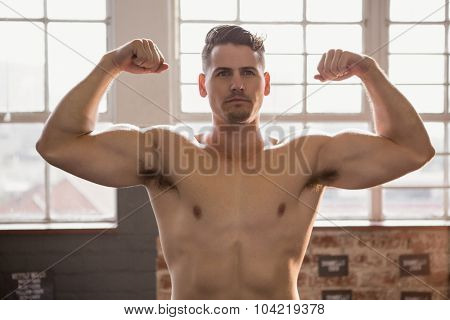 Muscular man showing biceps at the gym